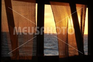 Sunset between curtains at sea - MeusPhoto