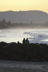 Couple watching sunset at sea in Byron Bay - MeusPhoto