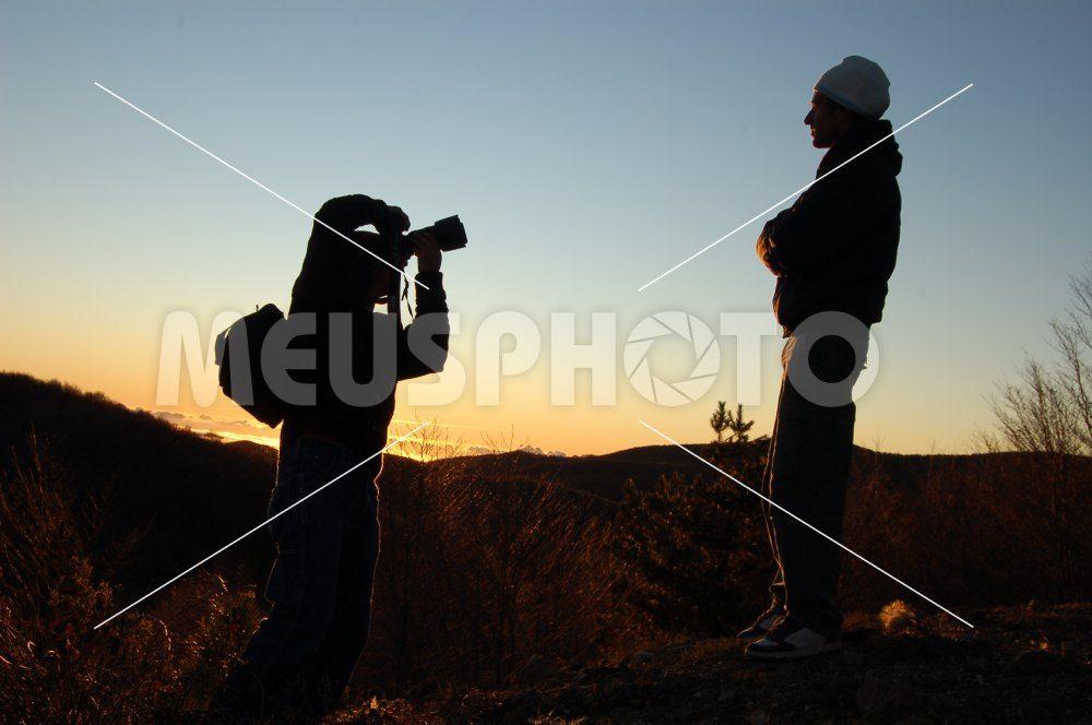 Photographer shooting a man at sunset - MeusPhoto